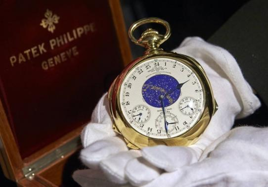 "File photo of a staff member holding ""The Henry Graves Supercomplication"" handmade watch by Patek Philippe at Sotheby's auction house in Geneva"