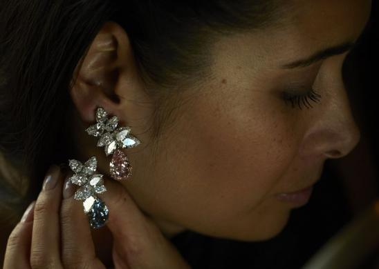 File picture of a Christie's staff member holding a Bulgari pear-shaped coloured diamond ear-pendants d in Geneva