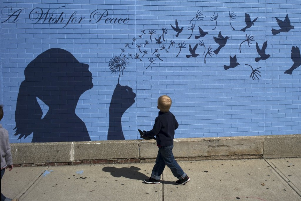 a-boy-looks-up-at-a-mural-reading-a-wish-for-peace-in-medford-massachusetts-september-15-2014