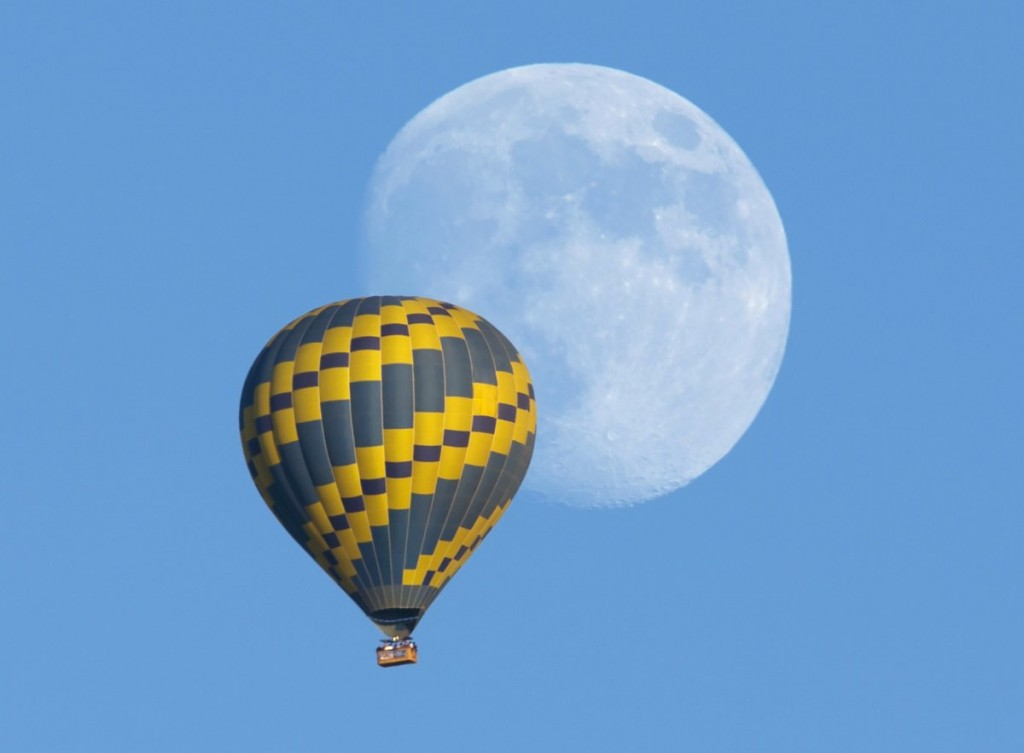 a-hot-air-balloon-floats-past-an-almost-full-rising-moon-on-a-warm-fall-evening-near-encinitas-california-on-october-5-2014