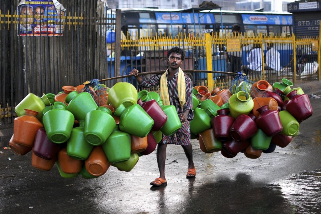 a-man-carries-empty-water-pitchers-for-sale-in-a-market-in-the-southern-indian-city-of-bangalore-on-october-9-2014
