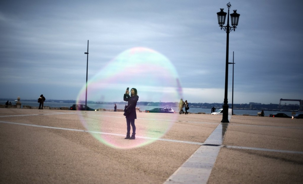 a-tourist-is-seen-through-a-soap-bubble-as-she-takes-a-picture-at-comercio-square-in-downtown-lisbon-on-november-18-2014