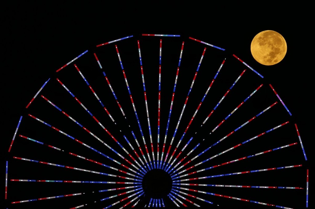 the-moon-is-pictured-behind-a-ferris-wheel-on-the-pier-in-santa-monica-california-after-a-total-lunar-eclipse-also-known-as-a-blood-moon-on-october-8-2014-the-coppery-reddish-color-the-moon-takes-is-made-as-it-passes-into-earths-shadow