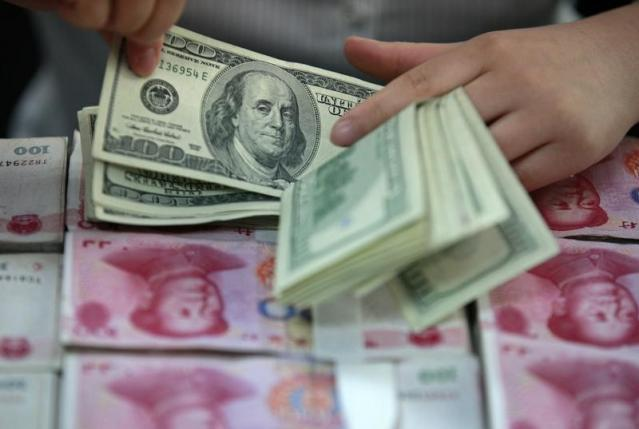 A bank clerk counts U.S. dollar banknotes on bundles of 100 Chinese yuan banknotes at a branch of a bank in Huaibei