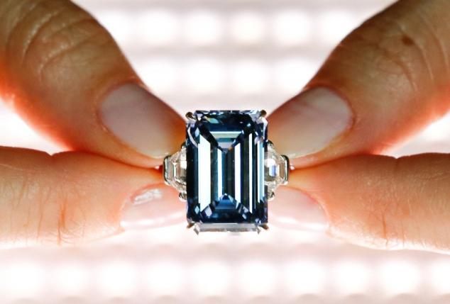 A Christie's employee poses with the 14.62 carats Oppenheimer Blue diamond during a preview in Geneva