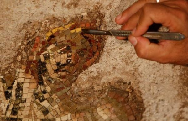"""File picture of a worker cleaning a mosaic mural depicting Apollo and the Muses found in an archaeological site under the """"Terme di Traiano"""" in downtown Rome"""