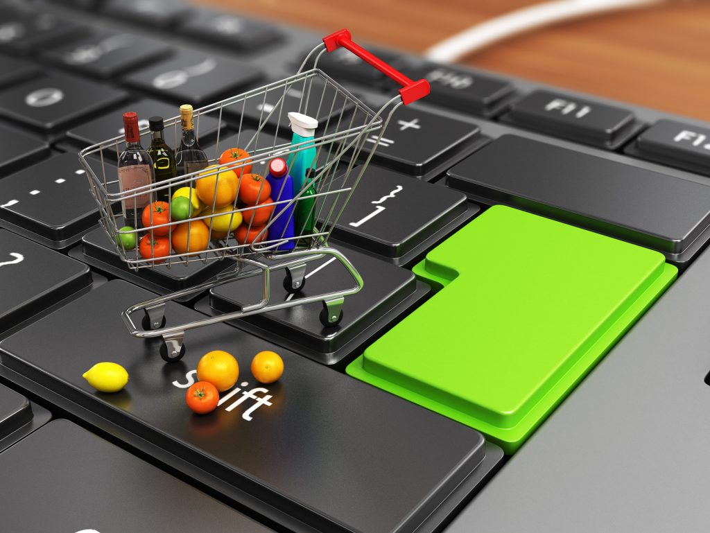 food basket on keyboard concept of electronic purchases