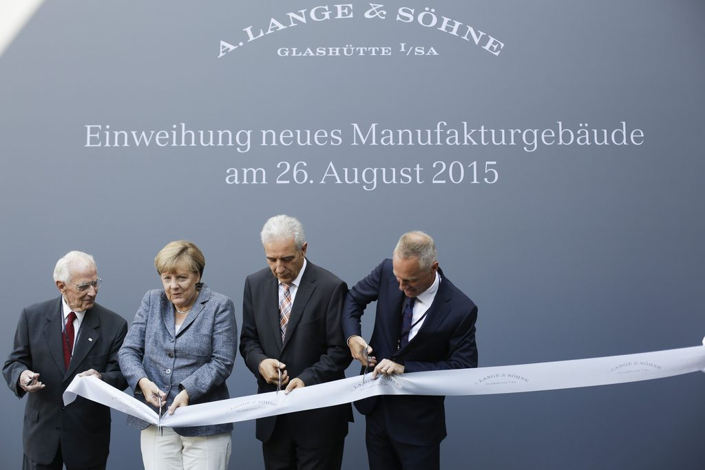 Walter Lange, refounder of Lange and Soehne watch makers, German Chancellor Angela Merkel, the State Premier of Saxony Stanislaw Tillich and the company's CEO Wilhelm Schmid cut the opening ribbon for the official opening of the new watch manufactory of Lange and Soehne watch makers in Glasshuette near Dresden, eastern Germany, on August 26, 2015. AFP PHOTO / POOL / MARKUS SCHREIBER