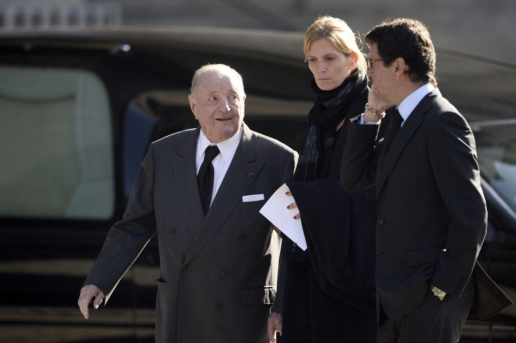 Belgian businessman Albert Frere (L) leaves with French fashion journalist Brune de Margerie (C) after attending the memorial service for Total's CEO Christophe de Margerie at the Saint-Sulpice church in Paris on October 27, 2014. Christophe de Margerie died in a plane accident in Russia on October 20, 2014. AFP PHOTO / STEPHANE DE SAKUTIN